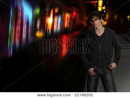 Young cool male model with goth emo eye makeup outdoors on city colorful street at night