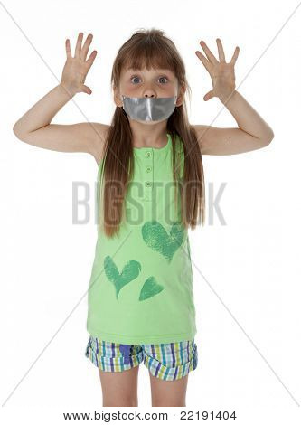 Young girl standing, mouth covered with duct tape, on white background.