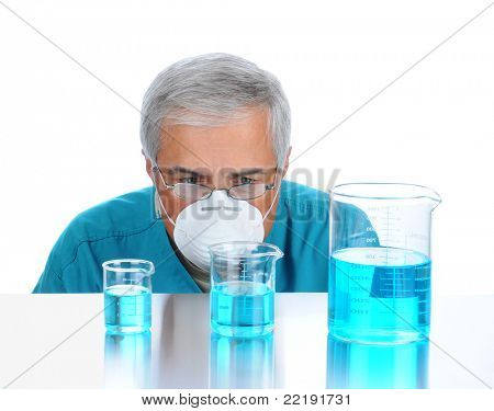 Scientist with protective mask examining laboratory beakers filled with a blue liquid, isolated on white with reflection. Man's face is at table top level.