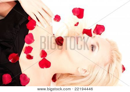 Portrait Of Beautiful Blonde Woman In Black Dress Lying In Rose Petals