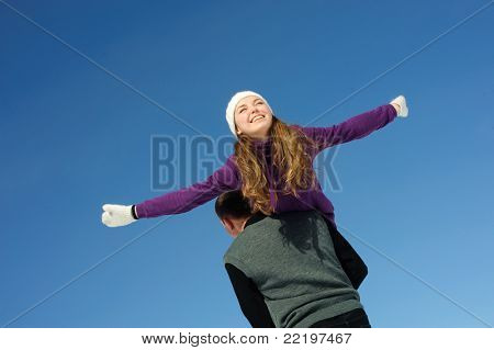 Happy woman enjoying life on the shoulder  of man