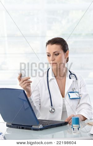 Female doctor sitting at table with laptop, looking at mobile phone, working.?