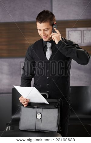 Businessman using mobile phone, smiling, reading document.?