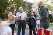 Middle aged and senior neighbours talking at a block party poster