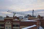 Tower Crane On A Background Of A Cloudy Sky Before Sunset. Winter Construction Of Residential Buildi poster