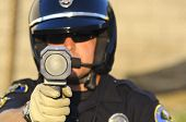 stock photo of guns  - a police officer aiming his radar gun at traffic - JPG