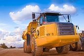 foto of oversize load  - yellow trucks on a field with beautiful blue sky - JPG
