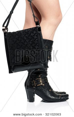 Detail of standing woman wearing fashionable black boots posing on white