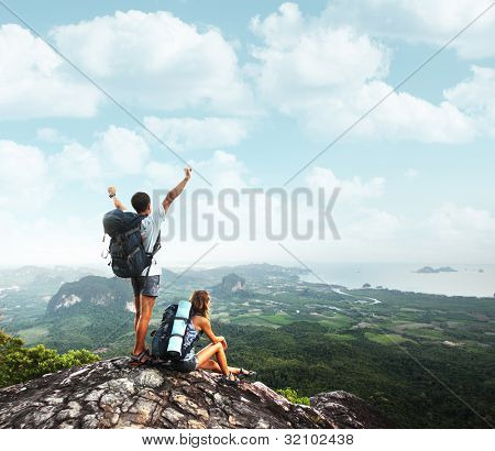 Two young backpackers enjoying a valley view from top of a mountain