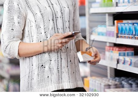 Mid-section of woman holding medication box and dialing on cell phone
