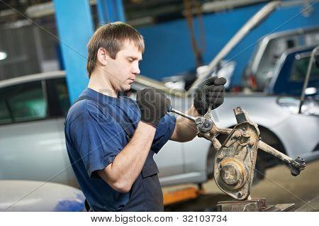 trabalhador mecânico automotivo aperte o parafuso com uma chave durante a manutenção do automóvel carro no rep alavanca