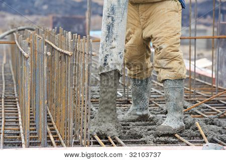 builder worker with tube from truck mounted concrete pump pouring cement into formwork reinforcement