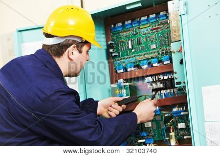 One electrician builder at work with multimeter checking current and voltage power at electric line distribution fuseboard