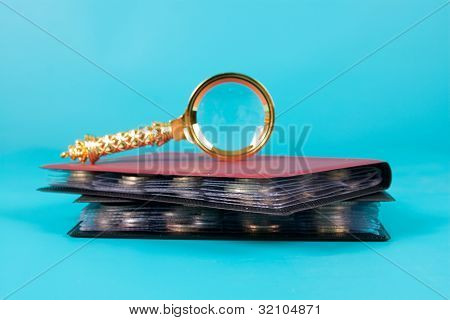 Magnifying Glass And Albums With A Collection Of Coins
