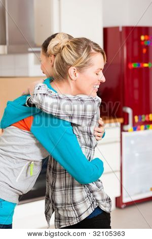 Two happy female friends moving in an apartment, they hug each other since everything is done
