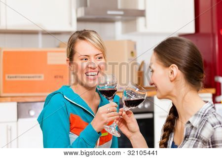 Two happy female friends moving in an apartment, they are drinking wine