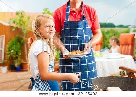 Familia feliz con una barbacoa en verano; el padre y un hijo en la parrilla