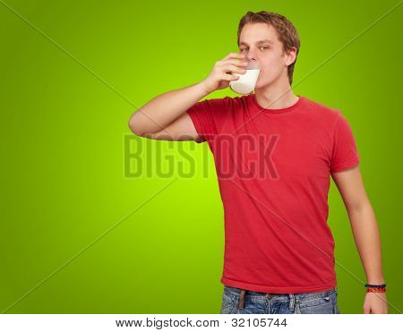 portrait of a young man drinking milk over a green background