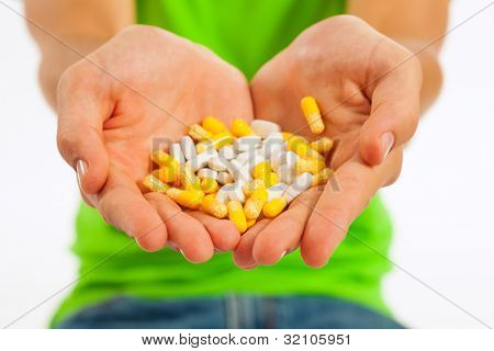 Young man is holding pills in his hand; focus on the hand