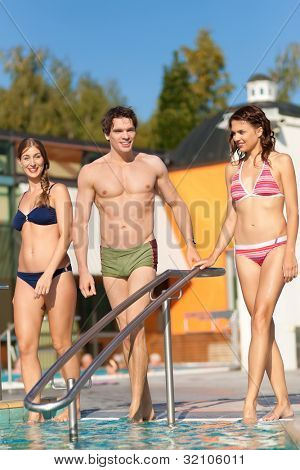 Two happy young women and a man - friends - walking into the water of a swimming pool; they are wearing swimwear