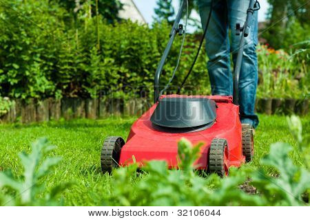 Young man - only legs to be seen - is mowing the lawn in summer with a mowing machine