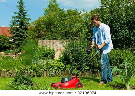 Young man is mowing the lawn in summer with a mowing machine