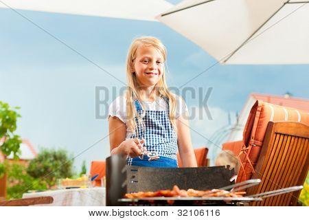 Familia feliz con una barbacoa en verano; la hija está de pie en el grill