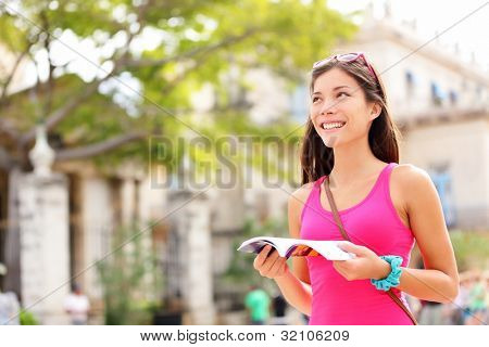 Tourist happy reading guide book. Woman traveler looking at copy space. Young female on vacation in Plaza de Armas, Old Havana, Habana, Cuba. Mixed race Asian / Caucasian young woman.