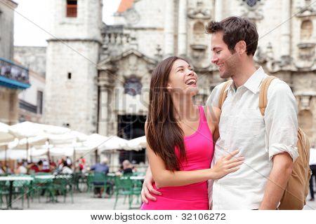 Tourists - happy couple in Cuba. Havana having fun during travel. Young interracial couple, Asian woman, Caucasian man, Plaza de la Catedral, Old Havana.