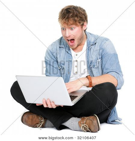 Man surprised with laptop computer looking at screen excited and happy in disbelief. Funny image of young Caucasian male student model sitting on floor isolated on white background.