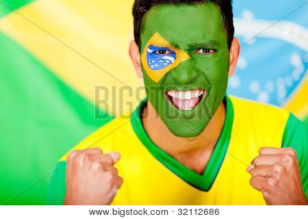 Happy Brazilian man with the flag painted on his face