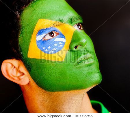 Proud Brazilian male with flag painted on his face - isolated over black