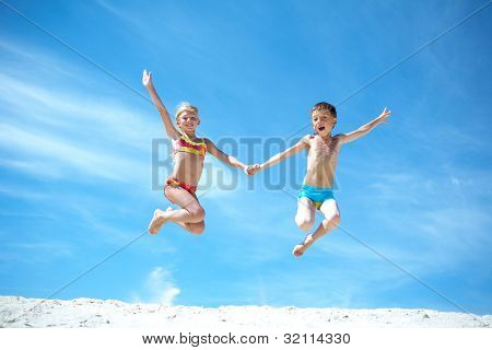 Photo of happy siblings jumping over sand and looking at camera
