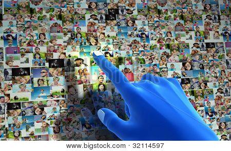 Red social. Mano azul apuntando a la pantalla llena de gente, caras