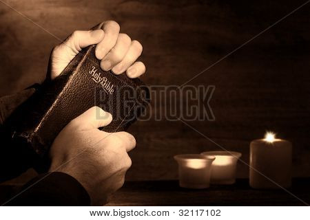 Praying Man Hands Holding And Clinching Old Bible