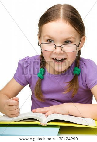 Cute little girl hits a book with fist showing her aggressive emotions, isolated over white