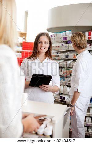 Retrato de mujer farmacéutico con Tablet Pc mientras asistía a la cliente.