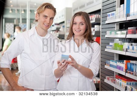 Two Pharmacists With Pharmaceuticals In Hand Consulting Each Other In A Pharmacy.