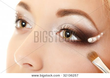 beauty makeup portrait of young beautiful woman with hand of esthetician applying eyes shadow with brush isolated on white background