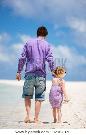 Father and his little daughter walking at beach