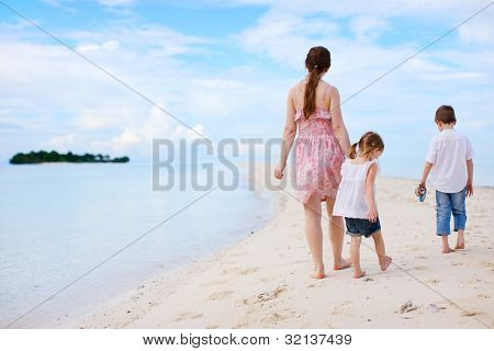 Back view of mother and two kids walking at beach
