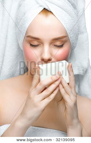 Portrait of young beautiful woman in white towel holding soap on her palm. Isolated on white background