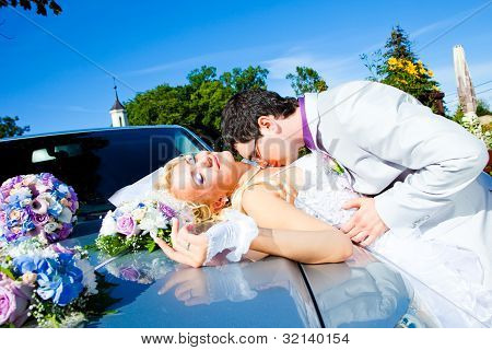 Groom And Bride Kissing On A Car Cowl