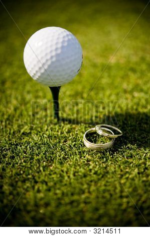 Wedding Rings Lying Next To A Golf Ball On Tee