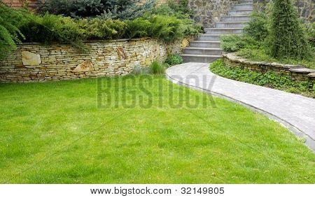 Camino de piedra jardín con pasto creciendo entre las piedras