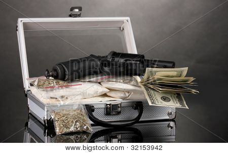 Cocaine and marijuana with gun in a suitcase on grey background