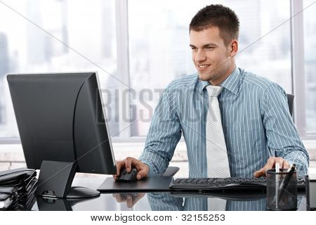 Young businessman sitting at desk in modern office, working on computer, smiling.
