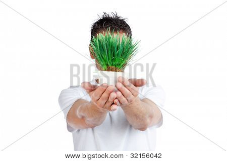 Man holding pot of green plant against white background.