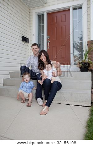 Portrait Of Sweet Family Sitting In Front Of Their House.