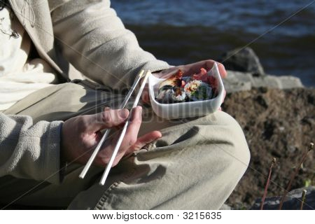 Man Eating Sushi Sitting On A Beach
